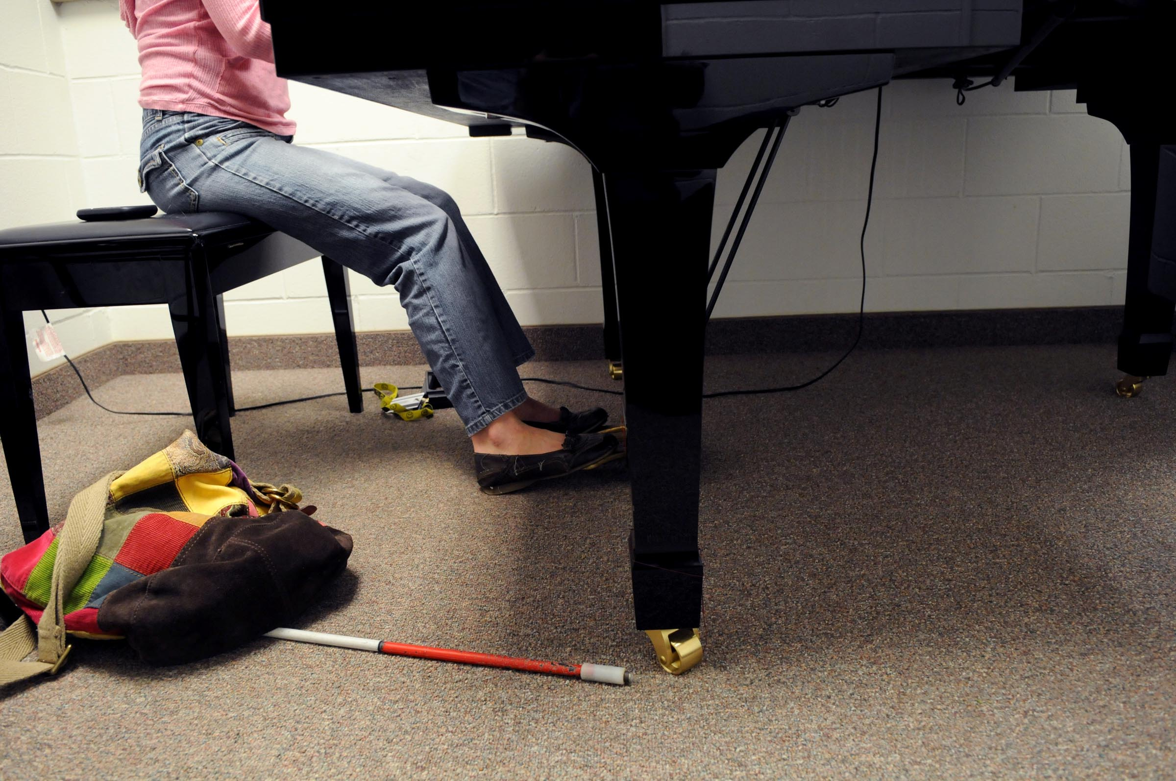 Piano player with white tipped cane