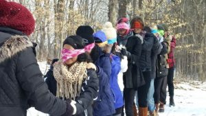 One student leading a line of blindfolded students in winter experiential education activity.