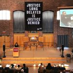 "Banner hangs in Hoversten Chapel reading ""Justice long delayed is justice denied."""